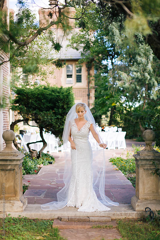 Bride in Garden Courtyard  by Gabrielle Lutze for Stocksy United