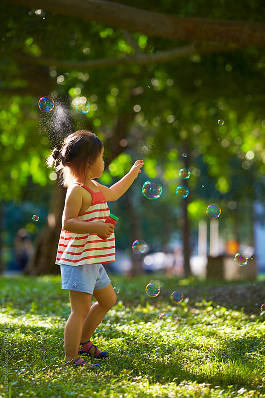 adorable little girl playing with bubble outdoor in the sunny park by Bo Bo for Stocksy United