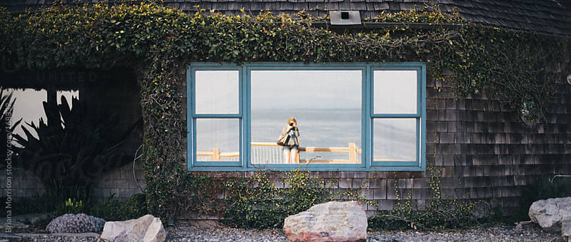 Reflection of a Woman and Ocean in Window of House by Briana Morrison for Stocksy United