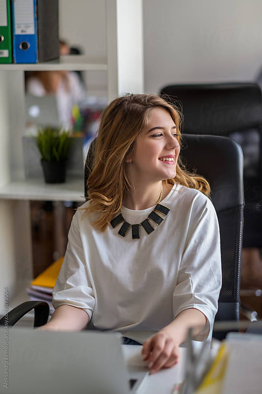 Beautiful Smiling Woman Sitting at the Desk in the Office by Aleksandra Jankovic for Stocksy United