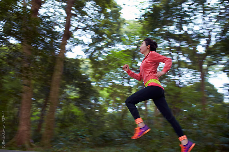 young asian woman running in the park by Bo Bo for Stocksy United