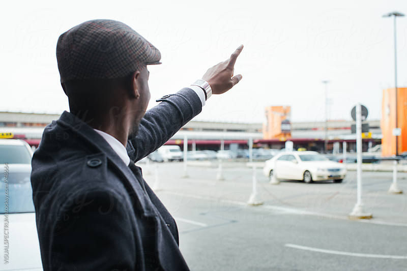 Stylish Black Businessman Waving Down Taxi at Airport by Julien L. Balmer for Stocksy United