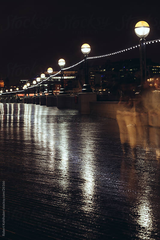 London at night with walking people by Robert Kohlhuber for Stocksy United