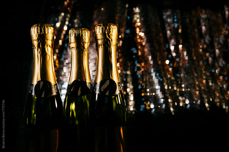 Bottles of champagne in front of a tinsel background by Beatrix Boros for Stocksy United