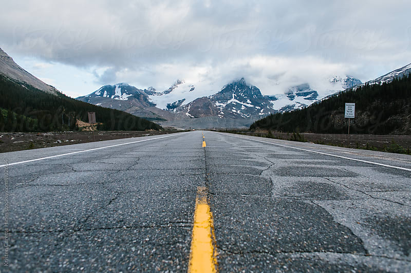 Paved road leading into the mountians by Kristen Curette Hines for Stocksy United