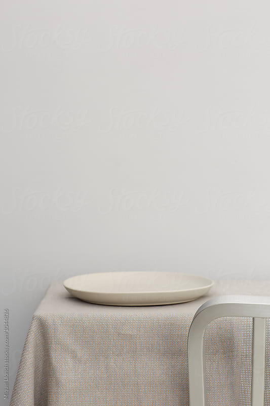 Detail of metallic chair and a table with a plate by Miquel Llonch for Stocksy United