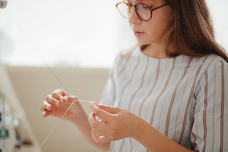 Young woman in retro glasses unravels the thread by Sergey Filimonov for Stocksy United