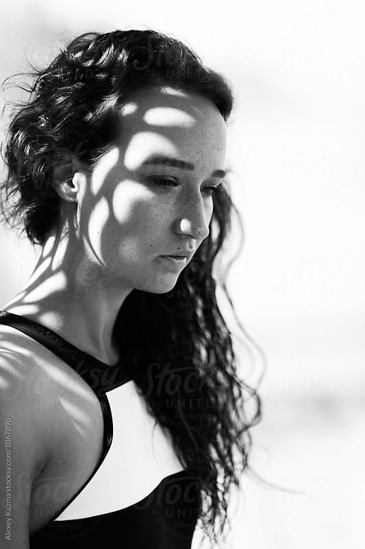 portrait of young woman on the beach by Alexey Kuzma for Stocksy United