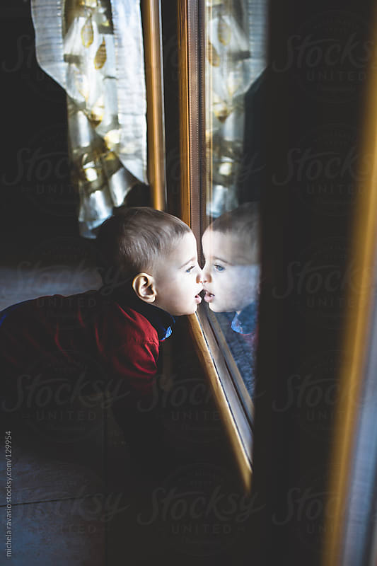 Baby looking through the window by michela ravasio for Stocksy United