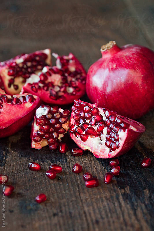 Broken Pomegranate on Wood Surface by Sara Remington for Stocksy United