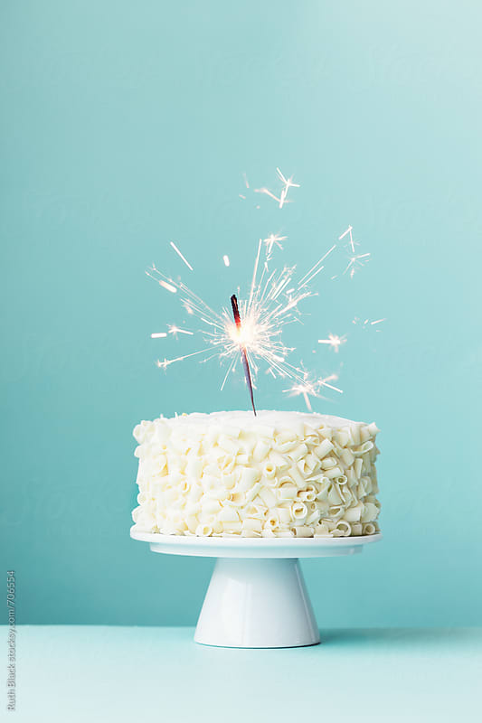 Cake with white chocolate curls and sparkler by Ruth Black for Stocksy United