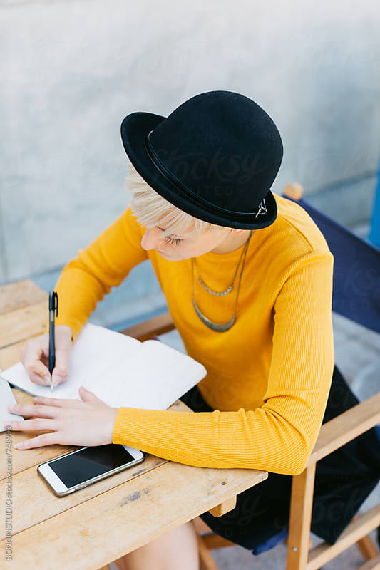 Woman writing on her notebook on the street. by BONNINSTUDIO for Stocksy United