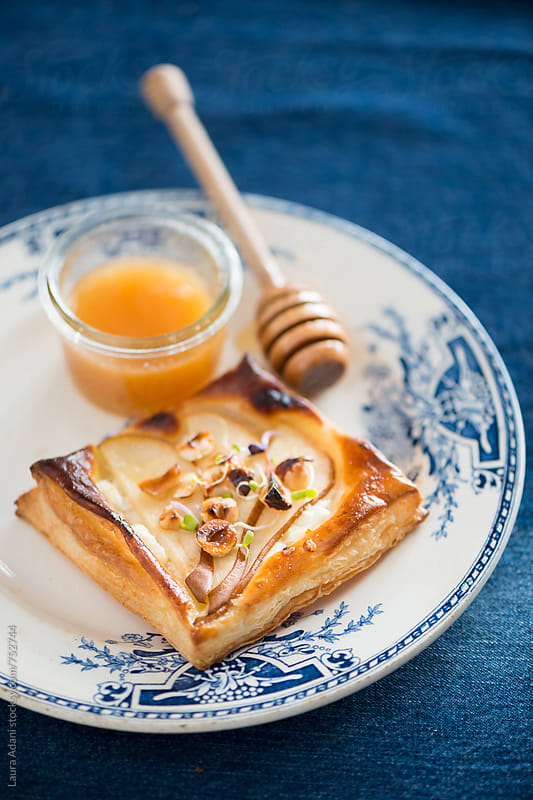 Mini tart with goat cheese, pears and honey by Laura Adani for Stocksy United