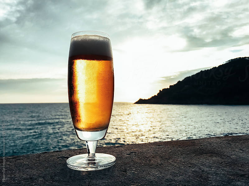 Glass of beer at against Ligurian sea by Paperclip Images for Stocksy United
