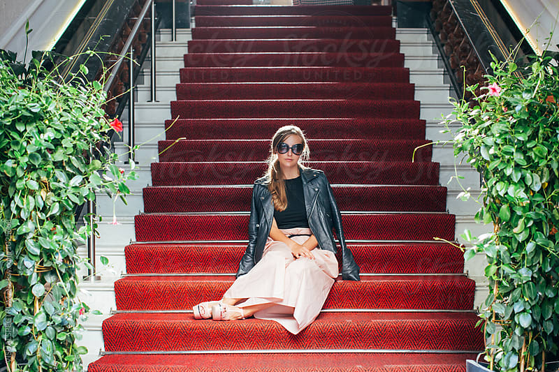 Young Elegant Caucasian Woman With Sunglasses Sitting on Red Carpet on Stairs by VISUALSPECTRUM for Stocksy United