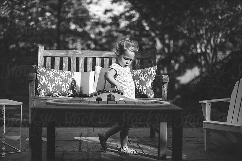 little girl playing with a toy train set in her backyard by Meaghan Curry for Stocksy United