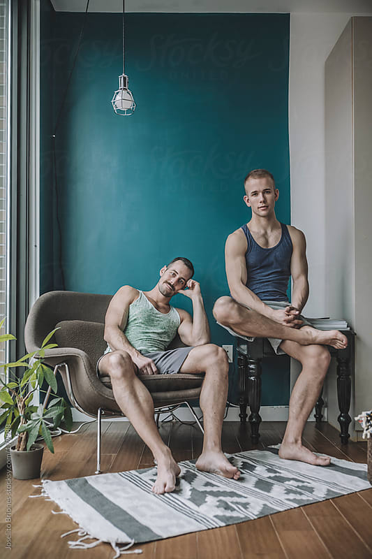 Informal and Casual Portrait of a Gay Male Couple at Home in their Living Room by Joselito Briones for Stocksy United