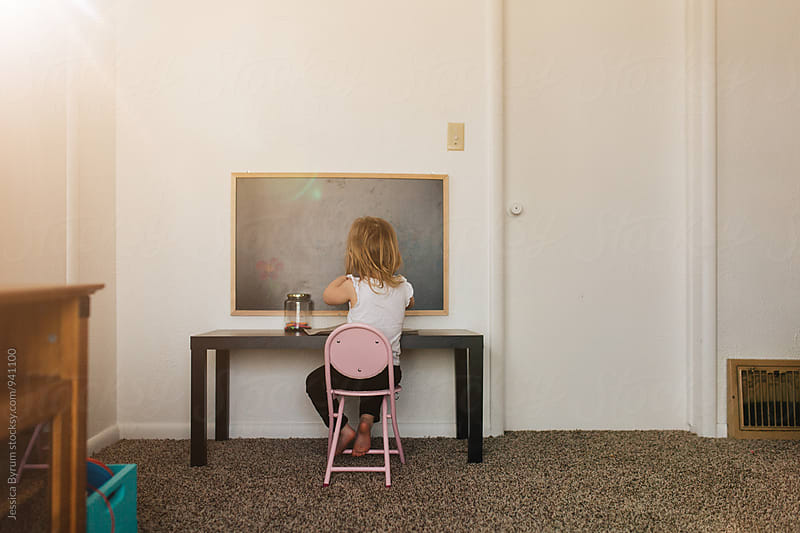 Small girl sitting at desk by Jessica Byrum for Stocksy United