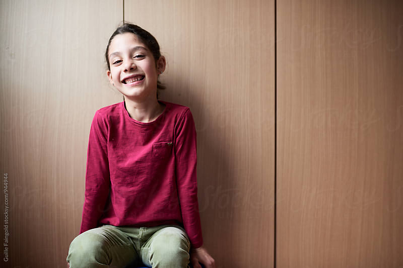 Smiling girl looking at camera by Guille Faingold for Stocksy United
