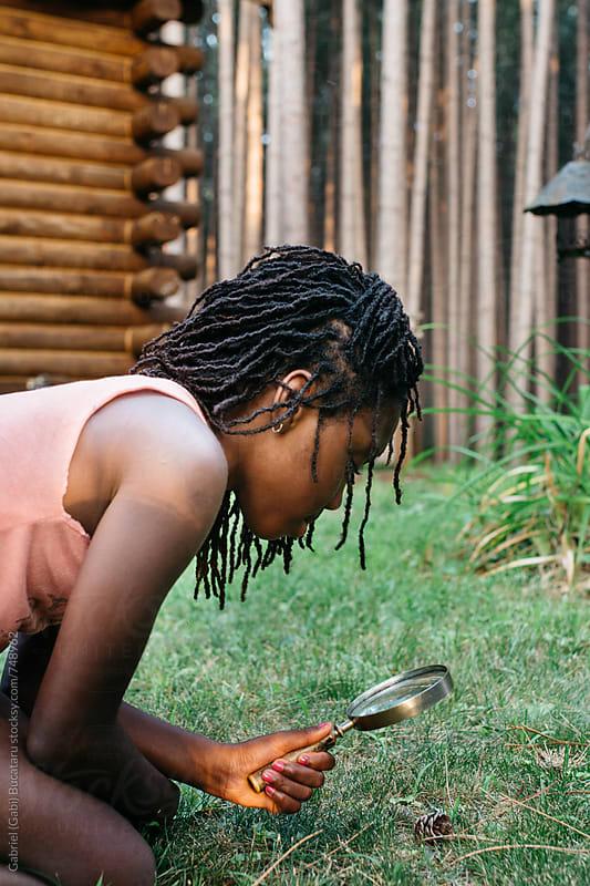 African American girl checking a bug through a magnifying glass by Gabriel (Gabi) Bucataru for Stocksy United