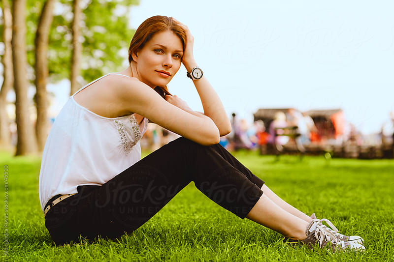 Young woman sitting on a grass by Aleksandra Kovac for Stocksy United