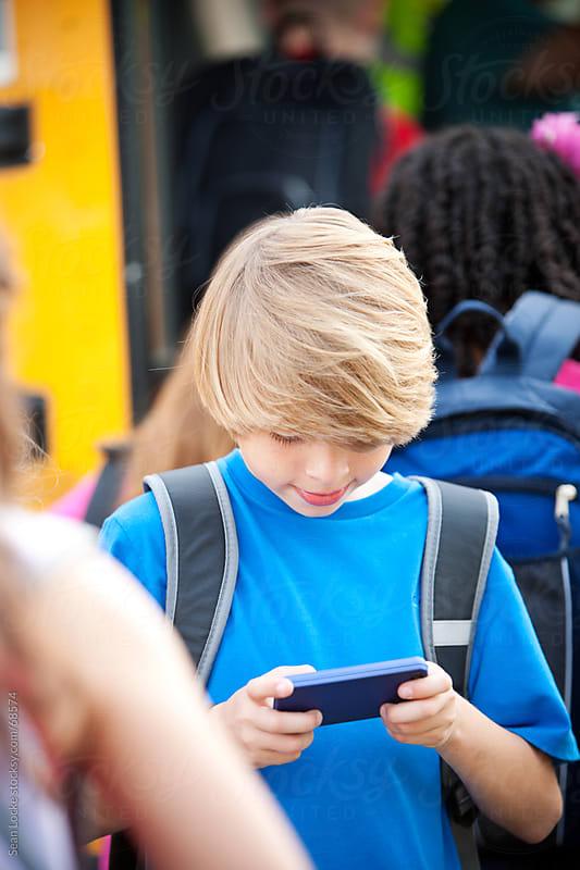 School Bus: Boy Checks Texts on Cell Phone by Sean Locke for Stocksy United