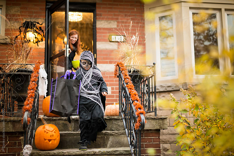 Boy Going Door To Door Trick or Treat at Halloween by JP Danko for Stocksy United