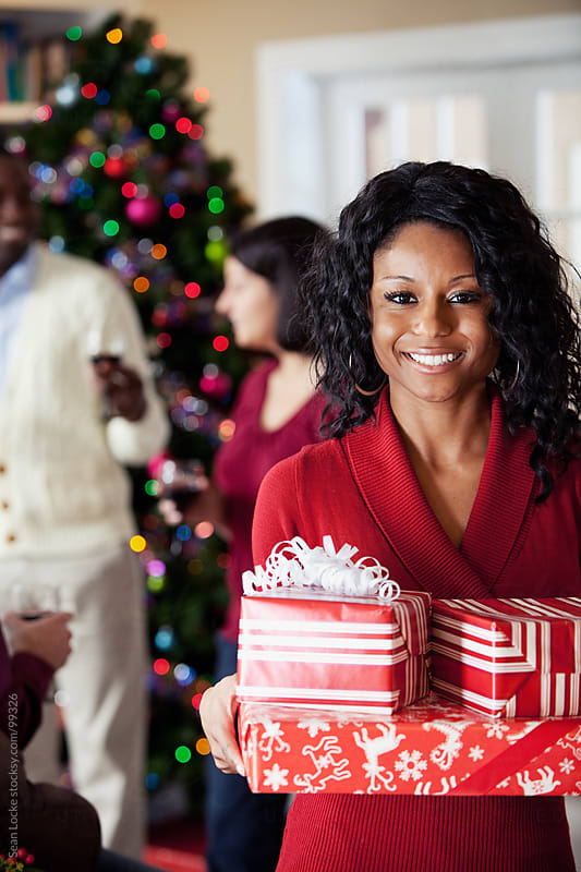 Christmas: Woman Holding Presents At Party by Sean Locke for Stocksy United