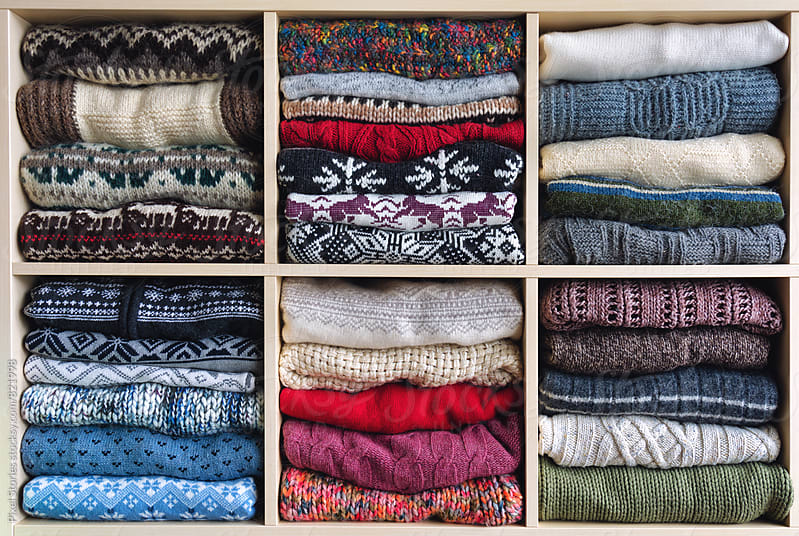 Winter-themed sweaters arranged on a shelf by Pixel Stories for Stocksy United
