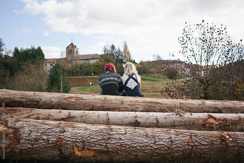 Love couple sitting together on some large tree trunks. by Koen Meershoek for Stocksy United