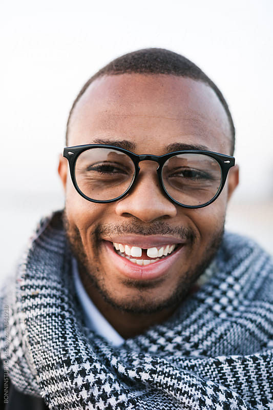 Closeup portrait of an african american man smiling on winter. by BONNINSTUDIO for Stocksy United