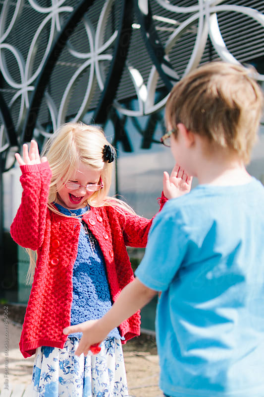 Twins, a boy and a girl, clap each others hands. by Julia Forsman for Stocksy United