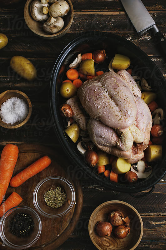 Roast chicken: Preparing a roast chicken meal in a roasting tin. by Darren Muir for Stocksy United
