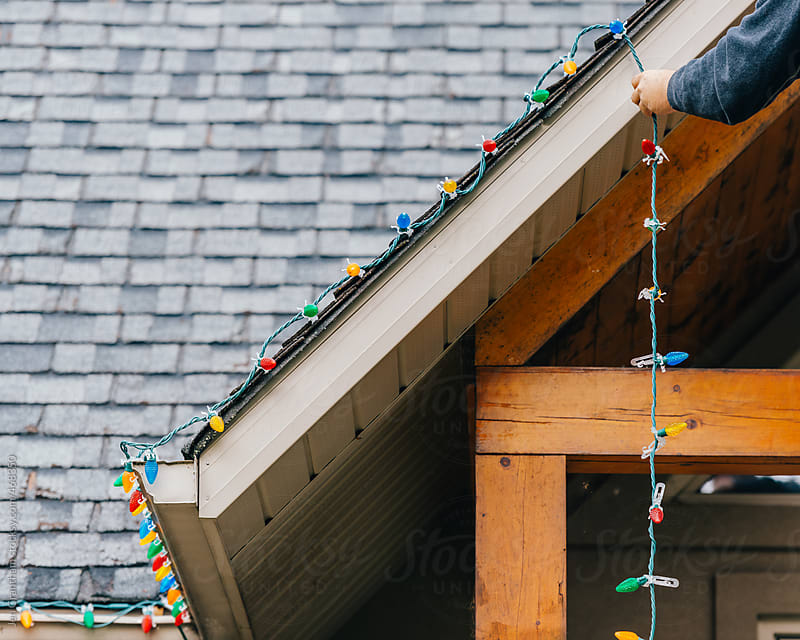 Man putting up exterior Christmas Lights by Jen Grantham for Stocksy United