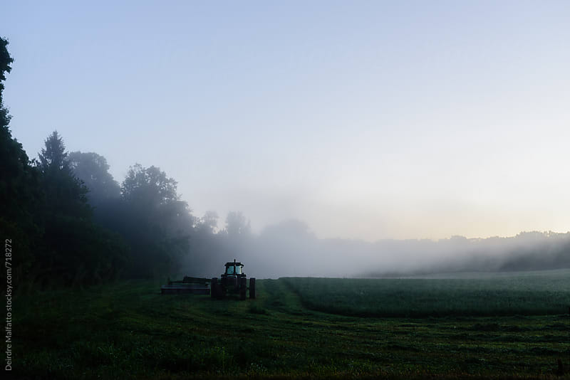 tractor in a misty field at sunrise by Deirdre Malfatto for Stocksy United