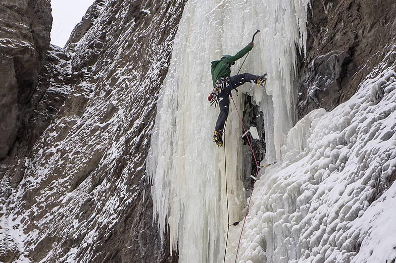Ice climber on steep curtain of ice, broken ice falling by Mick Follari for Stocksy United