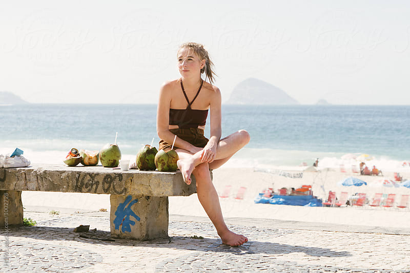 beautiful young blonde woman sits at the beach by HOWL for Stocksy United
