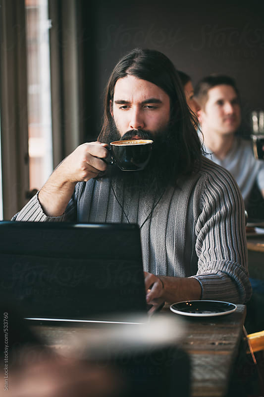 Cafe: Man On Laptop Takes A Drink Of Latte by Sean Locke for Stocksy United