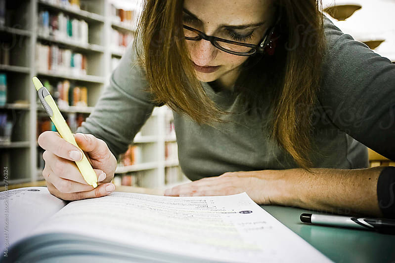 woman studies at library by Margaret Vincent for Stocksy United