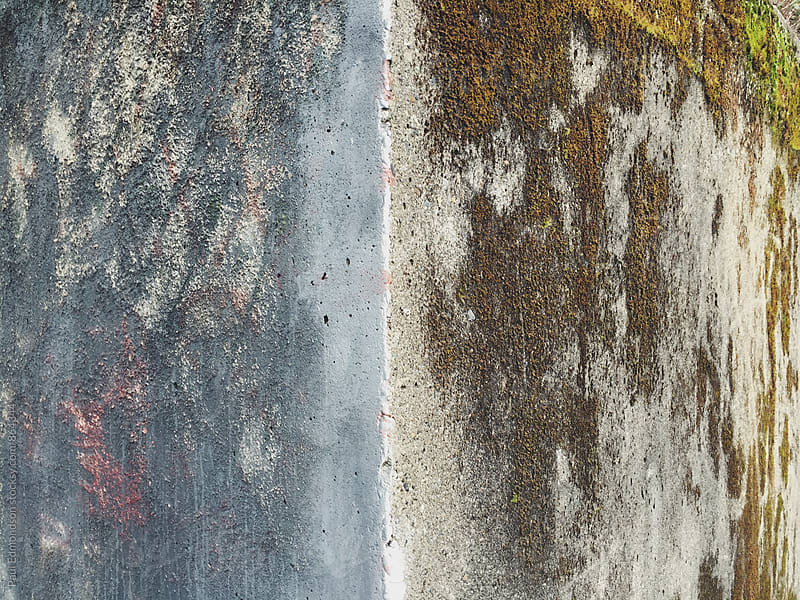 Corner of worn, moss covered concrete wall by Paul Edmondson for Stocksy United