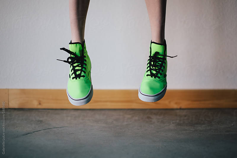 Jumping with Bright Green Sneakers  by Gabrielle Lutze for Stocksy United