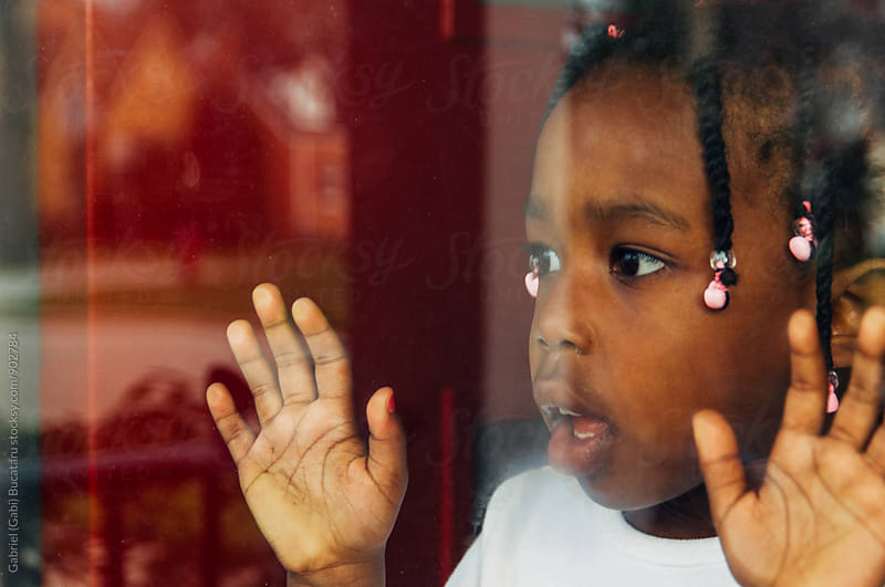 Black girl looking through a window by Gabriel (Gabi) Bucataru for Stocksy United
