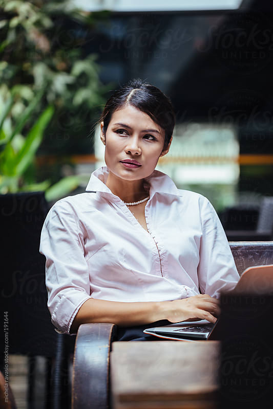 Business woman with her laptop, outdoors. by michela ravasio for Stocksy United