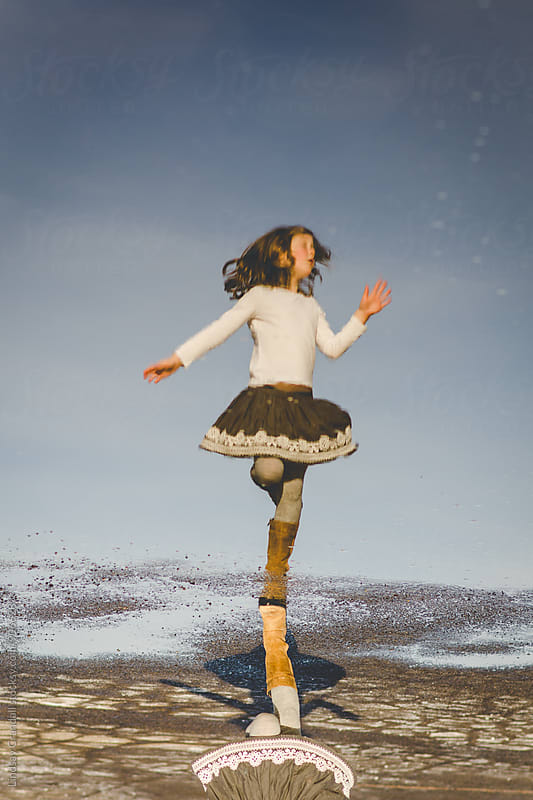 Young girl dancing in a reflection in a puddle by Lindsay Crandall for Stocksy United