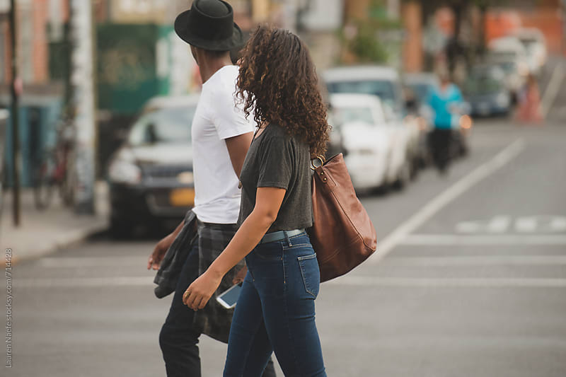 Young couple walking across the street by Lauren Naefe for Stocksy United