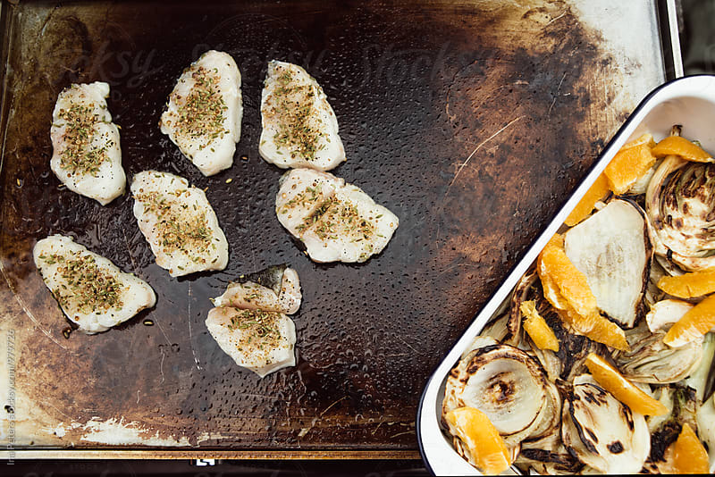 Food: Grilling herbed cod filets on a plancha by Ina Peters for Stocksy United