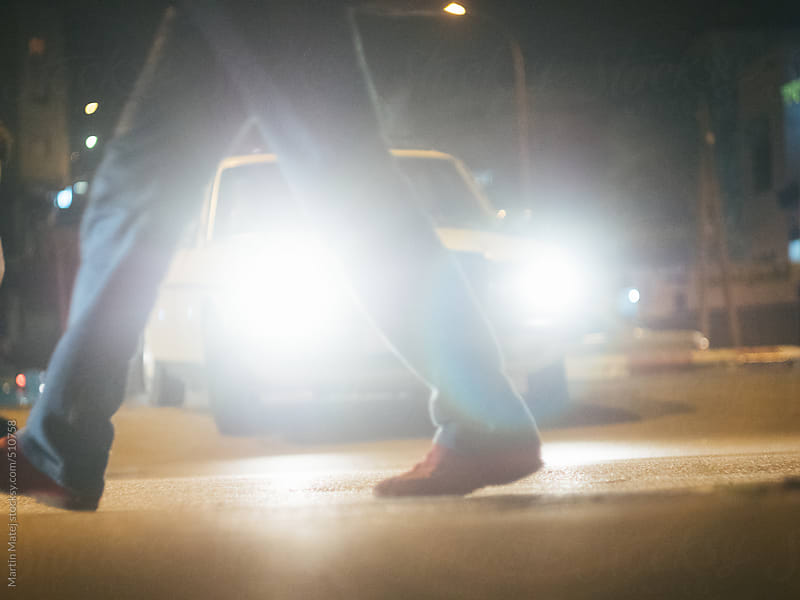 Cars light glowing through mans legs at night street by Martin Matej for Stocksy United