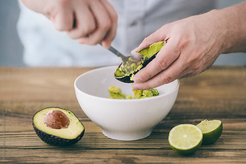 Man Preparing Guacamole with Avocados and Lime by Stephen Morris for Stocksy United