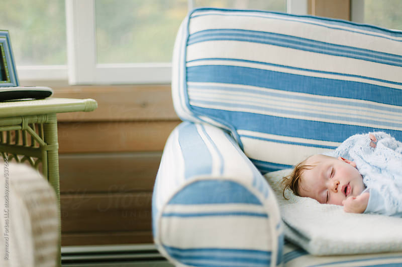 Portrait of Baby asleep on Couch by Raymond Forbes LLC for Stocksy United