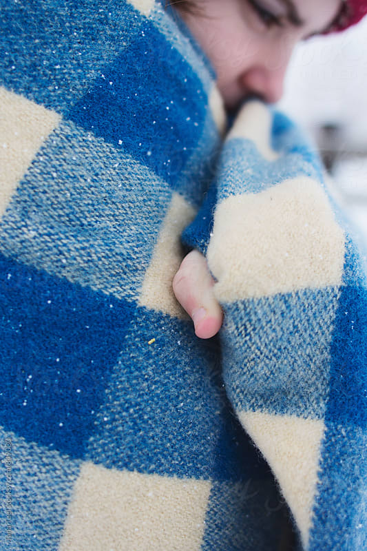 young woman's finger sticking out from wrapped blanket by Tana Teel for Stocksy United